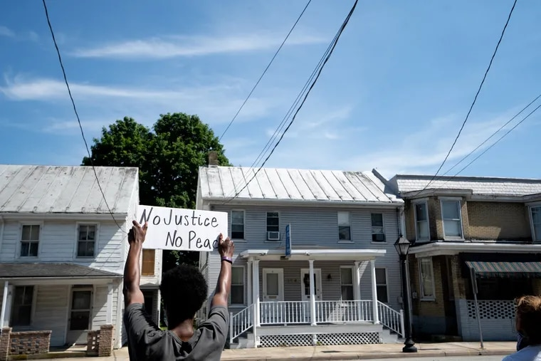 A man holds a sign in support of Black Lives Matter during a protest on King Street in Shippensburg, PA, June 9, 2020.