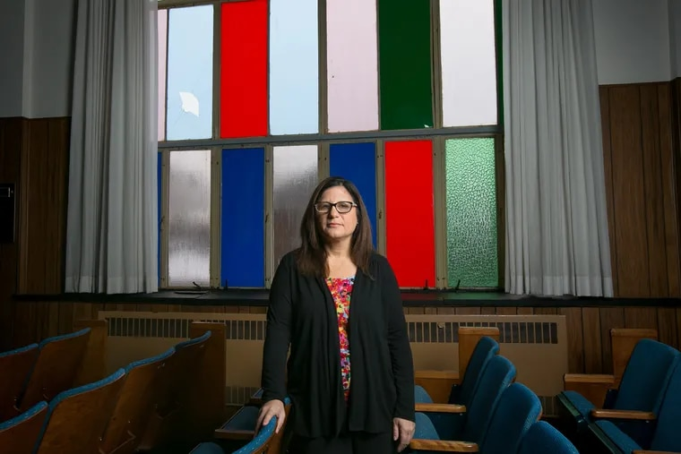 Rabbi Robyn Frisch shown here in front of two of the broken window panes at Temple Menorah Keneseth Chai, on Tuesday in Philadelphia.
