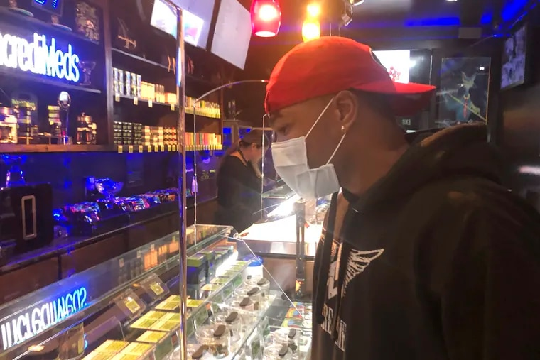 """A customer who wished to remain unidentified wears a mask while shopping at The Green Cross cannabis dispensary in San Francisco, Wednesday, March 18, 2020. As about 7 million people in the San Francisco Bay Area are under shelter-in-place orders, only allowed to leave their homes for crucial needs in an attempt to slow virus spread, marijuana stores remain open and are being considered """"essential services."""" (AP Photo/Haven Daley)"""