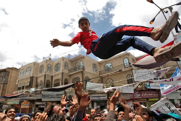 Demanding the resignation of Yemen's president, demonstrators toss a youth into the air in San'a. Saleh, in power for 32 years, warned that al-Qaeda may take over when he leaves.