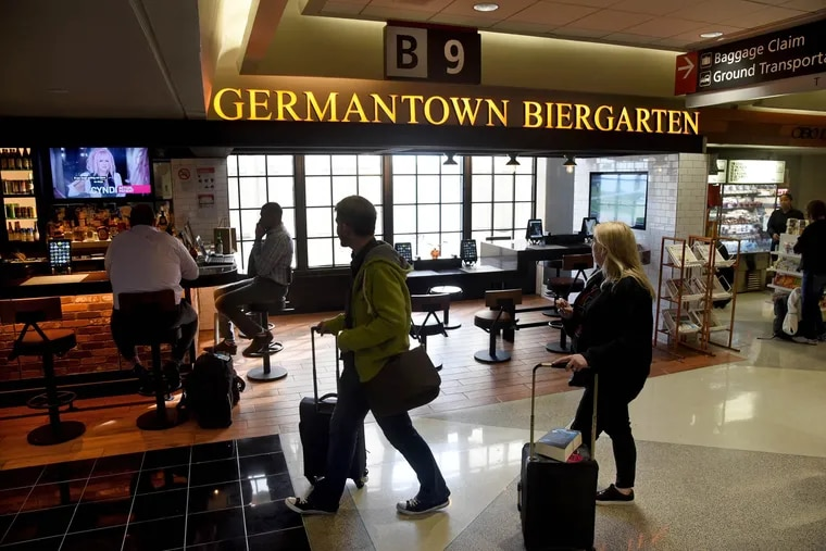 Travelers in Philadelphia International Airport stroll past the Germantown Biergarten, one of Terminal B's restaurants run by OTG. OTG workers are fighting for the right to take their employer to court.