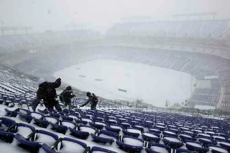 At M&T Bank Stadium in Baltimore, workers remove snow in preparation for a Ravens-Chicago Bears football game today.