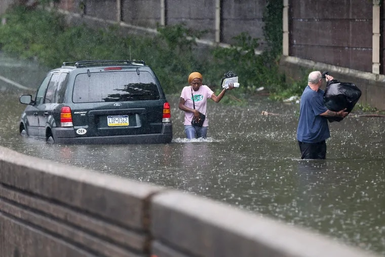 Bob Dugon (right) helps his friend Kiearra Price retrieve belongings from her car after it was caught in floodwaters on West Hunting Park Avenue at Ridge Avenue in North Philadelphia on Friday.