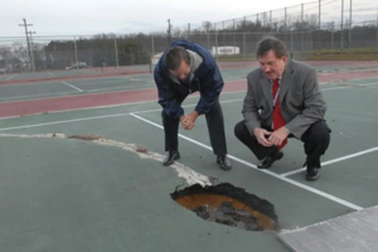 This tennis court at Highland Regional High in Blackwood isn't fit to use. Ralph Ross (right), Black Horse Pike superintendent, and buildings supervisor Bill Collins hope a state aid proposal helps.