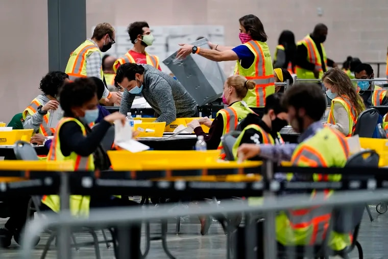 Philadelphia election workers process mail-in and absentee ballots for the general election, at the Pennsylvania Convention Center, Tuesday, Nov. 3, 2020, in Philadelphia.