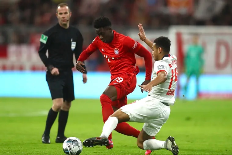 American midfielder Tyler Adams of RB Leipzig (right) playing against Canadian left back Alphonso Davies of Bayern Munich (center) in February.
