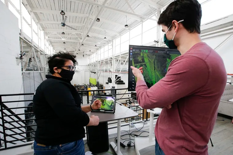 Robotics Software Engineer, Nour Hussein (left) and Director of R&D Software Brandon Duick of Exyn Technologies talk before a drone flight demonstration inside the company's South Philadelphia office on March 4, 2021.  Exyn Technologies makes aerial autonomous drones and software for use by miners that collect data and images in difficult environments.