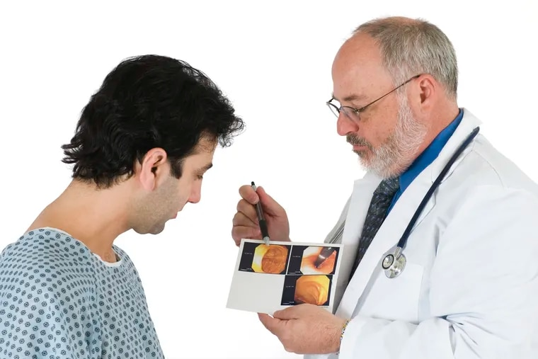 Doctor showing patient the images from his colonoscopy.
