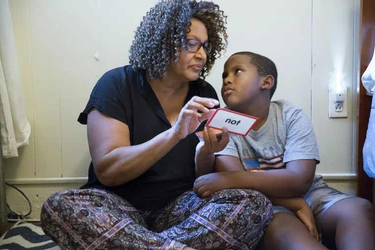 Avril Absolum uses flash cards to work with her son Jalen, who struggles to learn after being lead poisoned in his rental home.