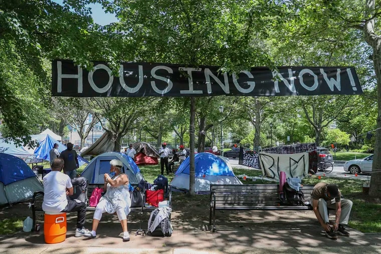 Signage hangs at the encampment set up at 22nd and Benjamin Franklin Parkway in Philadelphia on Friday, June 12, 2020. There is currently a community of homeless people and protesters living and volunteering there.