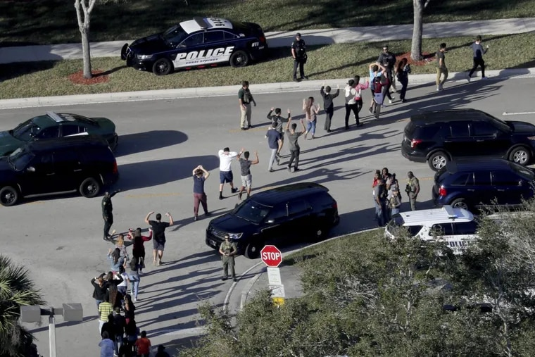 Students evacuate Marjory Stoneman Douglas High School in Parkland, Fla. on Feb. 14, 2018 after a gunman killed 17 people at the school.
