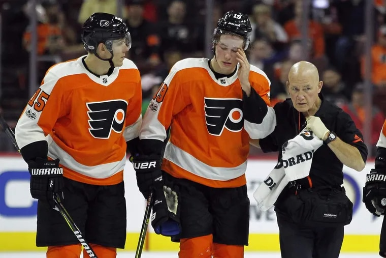 Philadelphia Flyers' Nolan Patrick, center, is helped of the ice by Jori Lehtera, left and a member of the training staff after suffering an injury during the third period of an NHL hockey game against the Anaheim Ducks', Tuesday, Oct. 24, 2017, in Philadelphia. Patrick returned to skate later in the game. The Ducks won 6-2. (AP Photo/Tom Mihalek) .