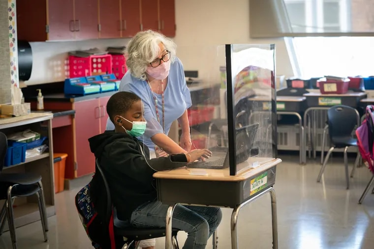 Second grade student Jaiden West, 8, with his teacher Bonnie Spears-Benedetto at Barry Elementary School in Philadelphia. The Philadelphia School District has said everyone will have to wear masks this school year.