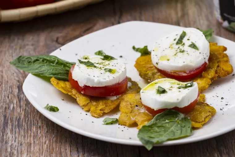 """A tropical Caprese """"patacone"""" is made with a slice of Būf buffalo mozzarella, basil and tomato layered atop a crispy fried plantain."""
