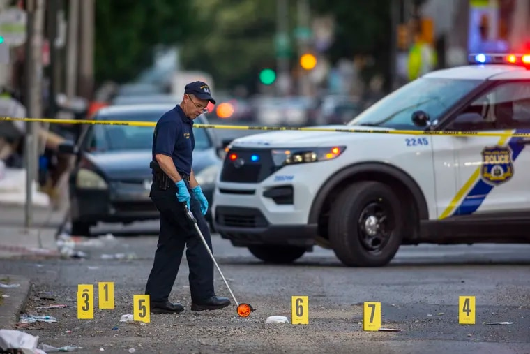 Crime scene officers gather and log evidence along Cecil B. Moore Avenue after a triple shooting left a woman dead and two men injured.