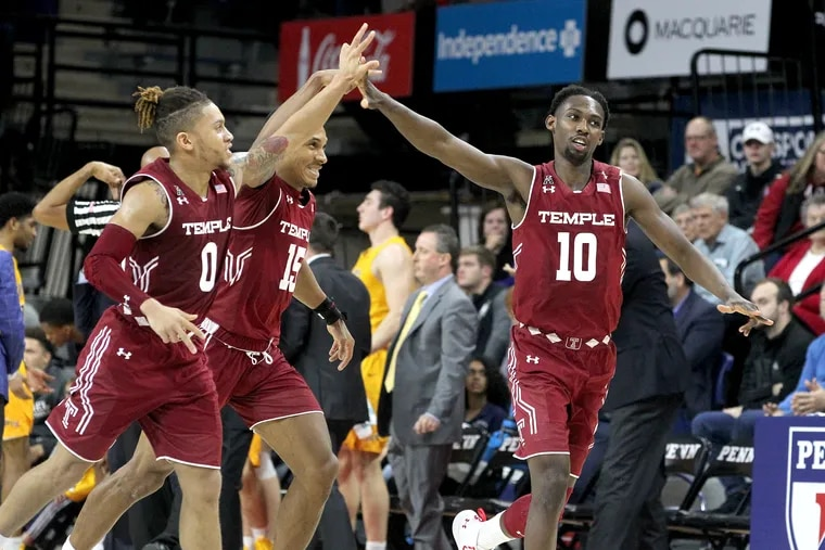Shizz Alston (right) is congratulated by Alani Moore (left) and Nate Pierre-Louis during Temple's last game, a win over Drexel on Dec. 22.