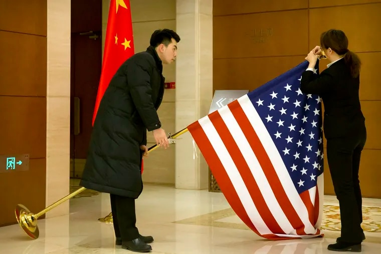 In this Feb. 14, 2019, file photo, Chinese staffers adjust a U.S. flag before the opening session of trade negotiations between U.S. and Chinese trade representatives at the Diaoyutai State Guesthouse in Beijing. Economist Mark Zandi looks at Trump's trade war with China and where the presidential candidates stand on trade, tariffs, and tax cuts, along with managing COVID-19. (AP Photo/Mark Schiefelbein, Pool, File)