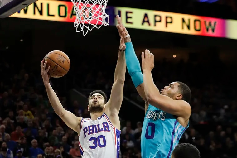 Sixers guard Furkan Korkmaz lays up the basketball past Charlotte Hornets forward Miles Bridges during the first quarter Sunday.