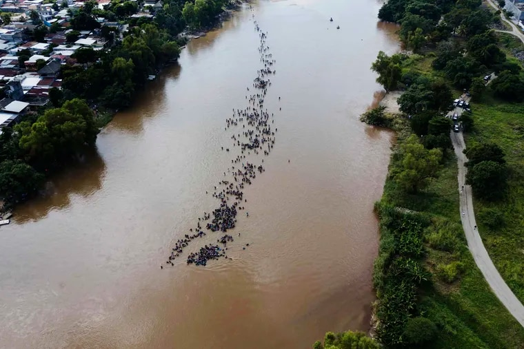 FILE - In this Oct. 29, 2018, file photo, a group of Central American migrants bound for the U.S. border wade together across the Suchiate River, which connects Guatemala and Mexico, in Tecun Uman, Guatemala. Border Patrol arrests in November jumped 78 percent from a year earlier to the highest level in Donald Trump's presidency, with families and children accounting for a majority for a third straight month. (AP Photo/Santiago Billy, File)