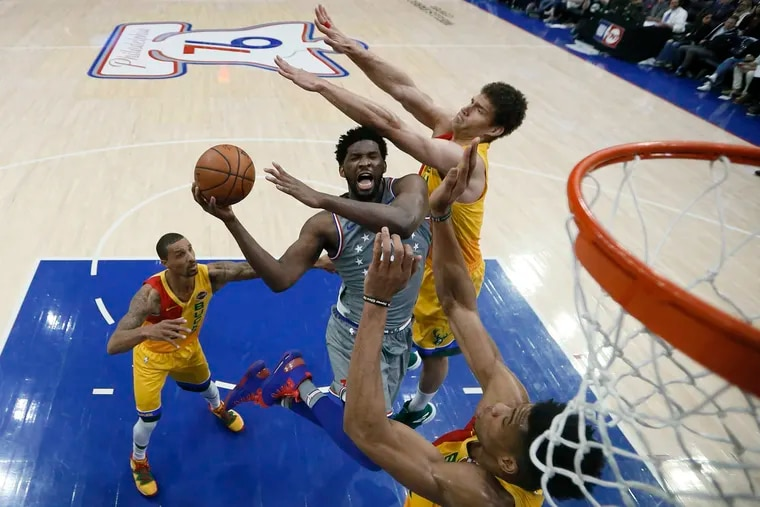 Sixers center Joel Embiid (center) shoots past Milwaukee's Brook Lopez (right) and Giannis Antetokounmpo (under basket) in April.