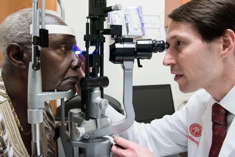 Jonathan Myers, of Wills Eye Hospital, examines Rose Carvalho in West Philadelphia. Medical practices are offering eye exams at primary-care offices or dental services during pediatric visits and taking blood pressure at barbershops.