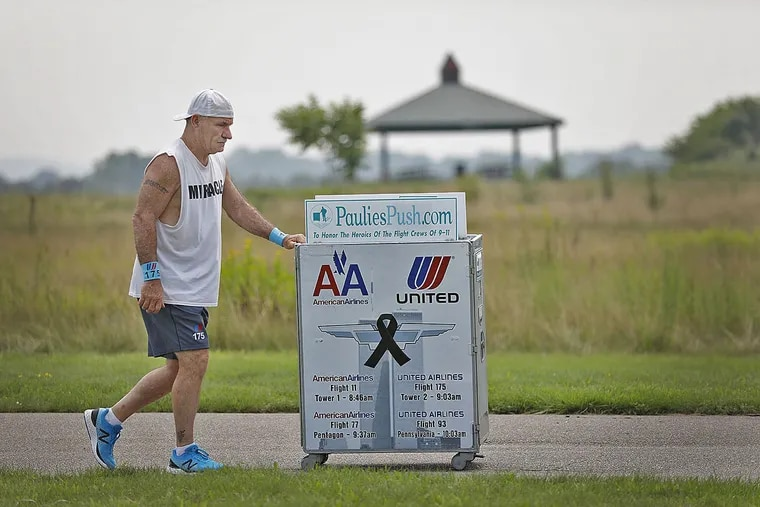 Paul Veneto pushes an airline service cart in Boston as training for his 220-mile walk from Boston to Ground Zero for the 20th anniversary of 9/11. Veneto is a former flight attendant who lost several colleagues when United Flight 175 was flown into the World Trade Center on Sept. 11, 2001.