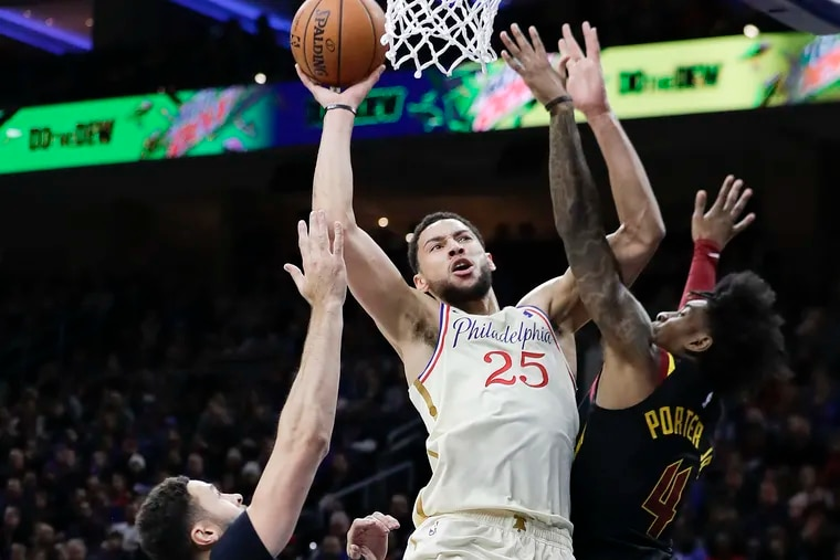 Sixers guard Ben Simmons drives to the basket against Cleveland's Kevin Porter Jr. (left) and Larry Nance Jr. during the first quarter.