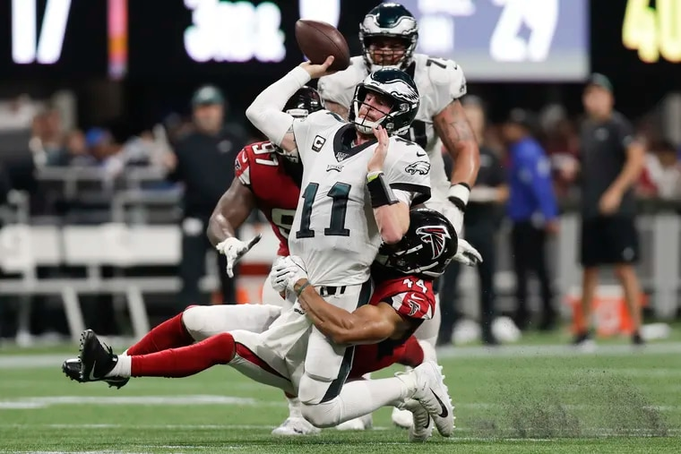 Eagles quarterback Carson Wentz gets rid of the football past Atlanta Falcons linebacker Vic Beasley during the fourth-quarter on Sunday, September 15, 2019 in Atlanta.