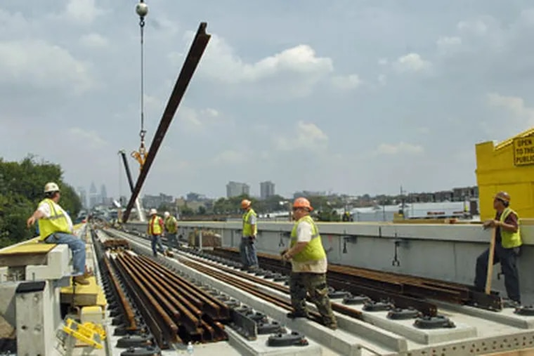Workmen guide a rail hoisted by a crane on the El tracks near 48th and Market Streets. (Jonathan Wilson/Inquirer)