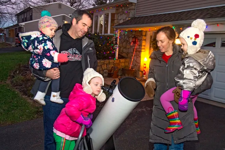 Rider Professor of Physics and Computer Science John Bochanski holds his daughter Claire, 1, as his oldest daughter Mary, 5, looks into the heavens hoping to see the conjunction of the planets Saturn and Junpiter through a Dobsonian Newtonian 8 inch telescope Sunday evening, December 6, 2020, outside their home in Holland, PA.  Aileen Bochanski holds daughter Sylvia, 3, who patiently waits her turn at the telescope.  ( CLEM MURRAY / For the Inquirer )