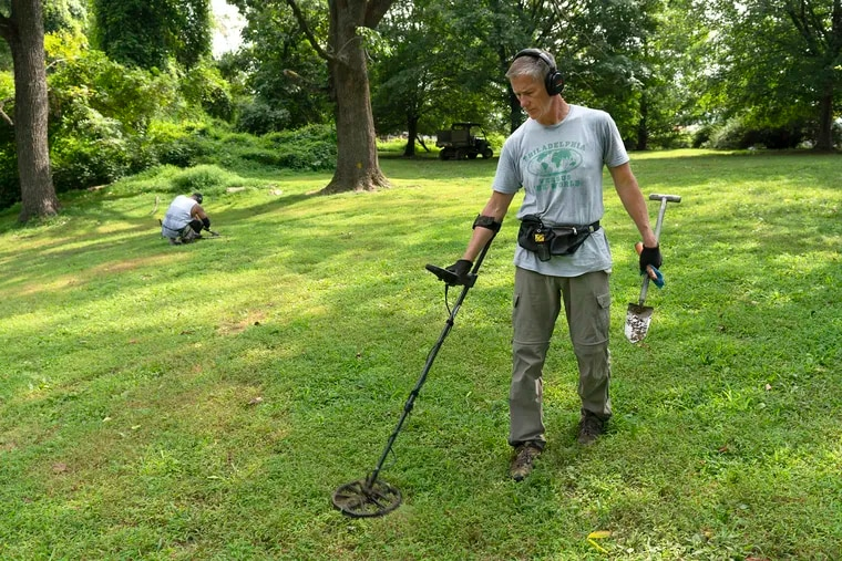 Richard Hageney of Downingtown searches for rings and coins using his metal detector at Pennypack Park. His friend Lee Taylor of Lancaster can also be seen in the background digging up a find.