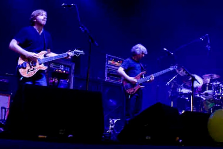 """On stage for a 23-song set: (from left) Trey Anastasio, Mike Gordon on bass, Jon Fishman on drums. Keyboardist Page McConnell is not visible. If it felt right, they went the distance on improv. """"Sand"""" alone clocked in at 22 minutes."""