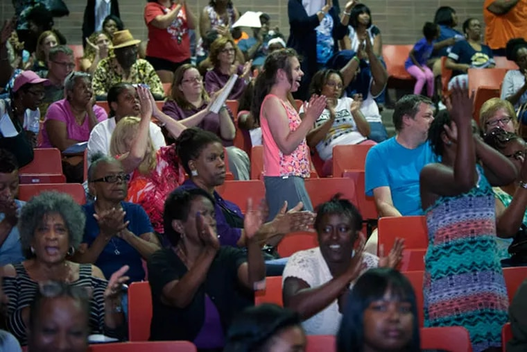 Members of the audience cheer a parent's comments during the Chester Upland school board meeting at Chester High School. (TRACIE VAN AUKEN/For The Inquirer/File)