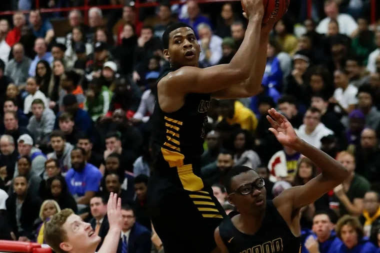 Archbishop Wood High's Muneer Newton (center) grabs the basketball over teammate Brennen Kersey (right) and Wildwood Catholic High's Jacob Hopping in the first-quarter during the Dajuan Wagner Play-By-Play Classic at Cherry Hill East High School on Monday, December 30, 2019.