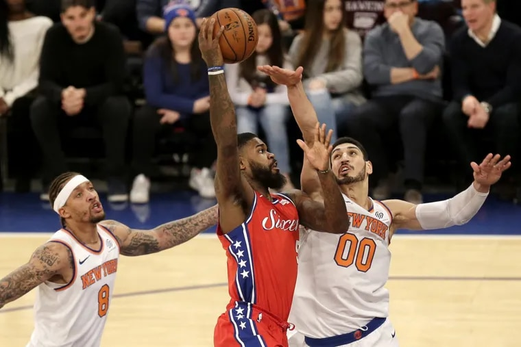 The Sixers' Amir Johnson, center, drives to the basket past New York Knicks Enes Kanter, right, and Michael Beasley during the first half.