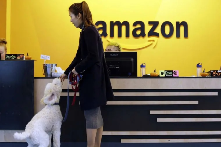 FILE - In this Wednesday, Oct. 11, 2017, file photo, an Amazon employee gives her dog a biscuit as the pair head into a company building, where dogs are welcome, in Seattle. Amazon announced Thursday, Jan. 18, 2018, that it has narrowed its hunt for a second headquarters to 20 locations, concentrated among cities in the U.S. East and Midwest. Toronto made the list as well, keeping the company's international options open.