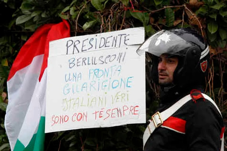 """Outside Milan's San Raffaele Hospital , a paramilitary police officer is flanked by a sign, next to an Italian flag, that reads: """"President Berlusconi, get well soon. Real Italians are with you always."""""""
