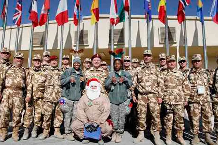 Soldiers of the NATO-led International Security Assistance Force join Santa Claus - a U.S. soldier beneath the costume - at Camp Phoenix. The troops celebrated Christmas with food, music, and improvisation.
