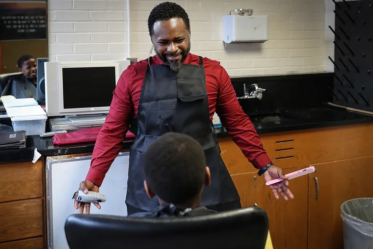 Principal Terrance Newton talks with student Michael Harley, 8, while giving him a haircut at Warner Elementary in Wilmington on Jan. 14, 2020.