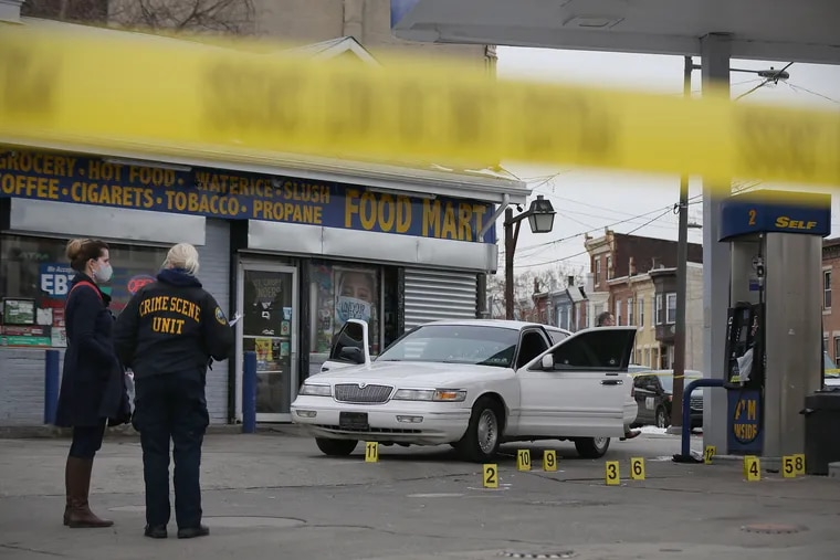 Philadelphia police investigate a fatal shooting at the gas station at 33rd and York Streets in Philadelphia's Strawberry Mansion section on Friday, Feb. 12, 2021. Police said a 38-year-old man was shot six times at 1:50 p.m. and taken to Temple University Hospital, where he was pronounced dead.