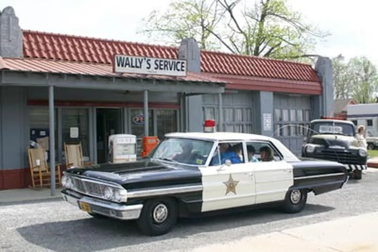 A squad car full of tourists pulls up to Wally's filling station in a 1962 Ford Galaxie 500, like the one Barney drove in the show's heyday, when the car was new and Gomer and Goober manned the pumps. The show still has a fond following. (Marshall S. Berdan)