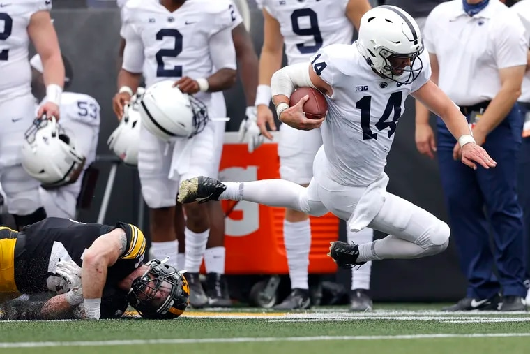 Iowa defensive back Jack Koerner (28) trips up Penn State quarterback Sean Clifford (14) on a run during the first half.