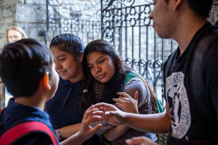 Keyri, right, puts her arm around her younger sister, Yoselin, shortly before leaving for the first day of school on Monday. Her brothers stand nearby at the Church of the Advocate, where the family lives in sanctuary.