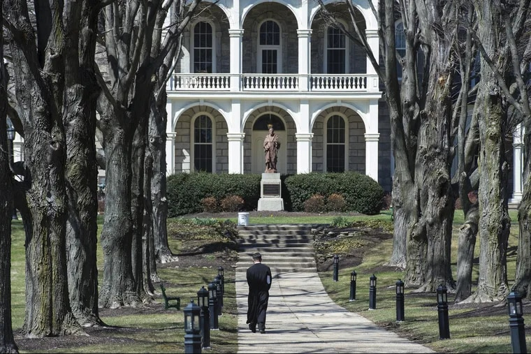 A seminarian at St. Charles Borromeo  Seminary in Wynnewood strolls the walkway to the Theology Building.