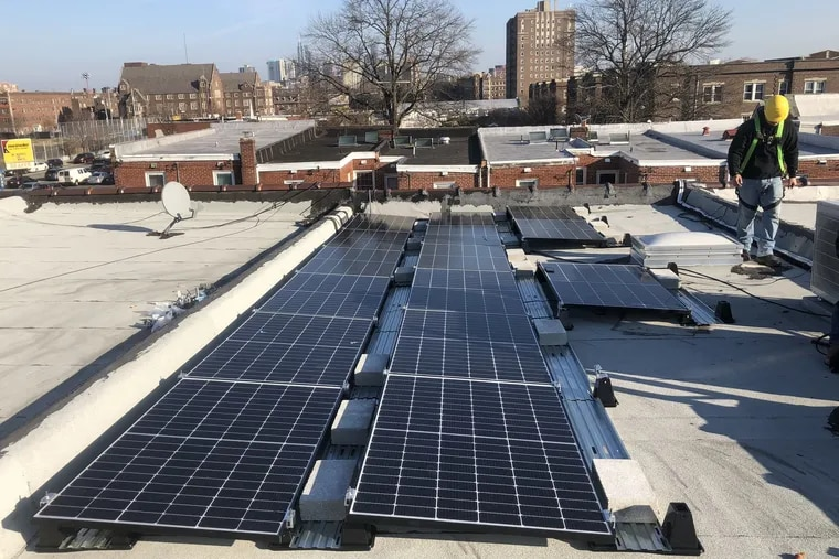 An employee of Solar States looks over solar panel installation on a West Philadelphia rooftop.