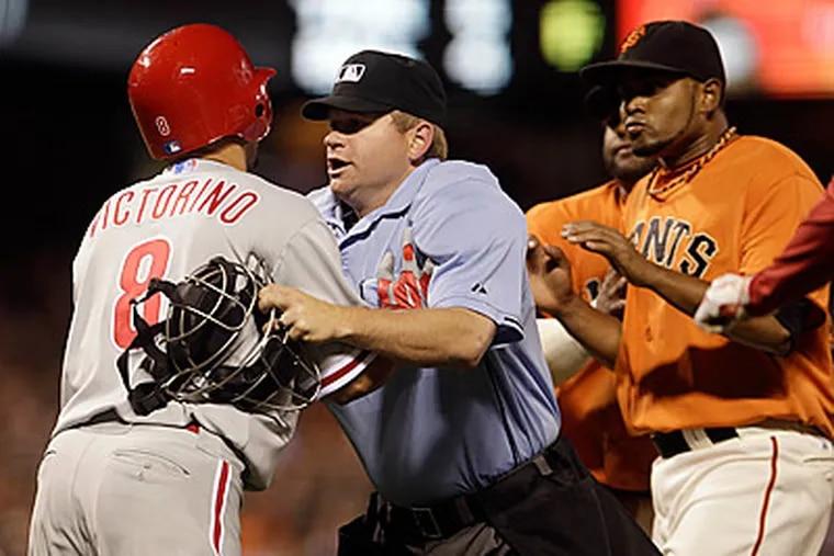 Shane Victorino is separated from Giants pitcher Ramon Ramirez. (AP Photo/Ben Margot)