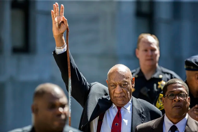 As Bill Cosby, center, leaves the Montgomery County Courthouse, he raises his arm in recognition to the crowd noise as he made his way to his SUV, after being found guilty on all three counts of sexual assualt during his retrial in Norristown, PA, on Thursday April 26, 2018.  MICHAEL BRYANT / Staff Photographer