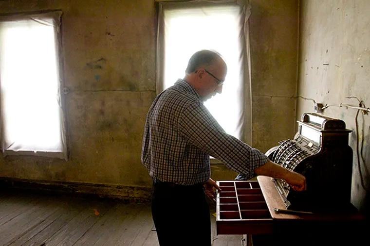 Fourth-generation proprietor of Baum's Dancewear, Peter Cohen, demonstrates a brass cash register, circa 1912, on Oct. 2, 2014. ( CHARLES FOX / Staff Photographer )