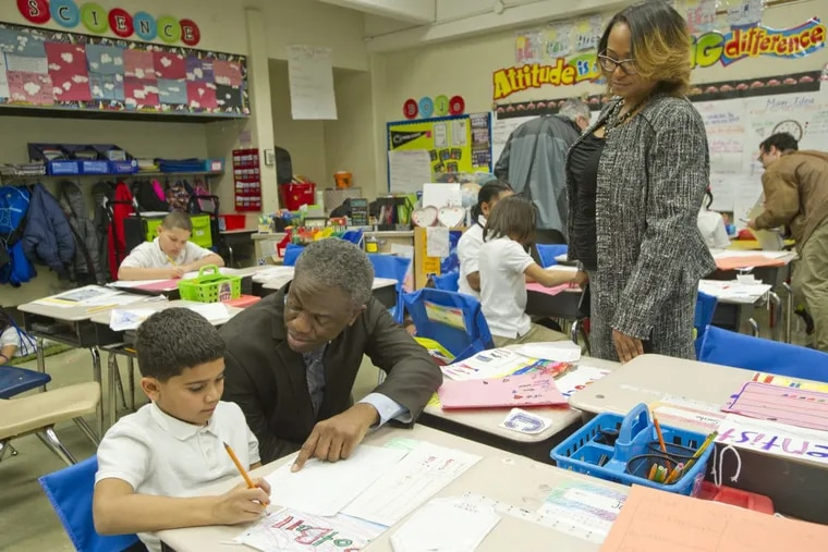 Assistant Superintendent Eric Becoats and Potter-Thomas Elementary School Principal Dywonne Davis-Harris talk to third grader Anthony Rodriguez, 8, before a ceremony honoring Potter-Thomas as one of the most improved schools in the city. AVI STEINHARDT / For the Inquirer and Daily News