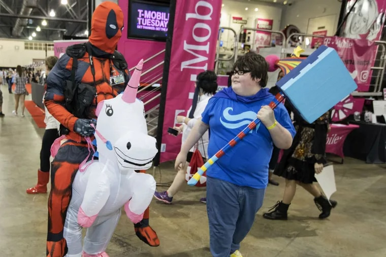 Paul Hogan, left, who was dressed as Deadpool on Buttercup, talk with Stephen Bukowski, who carries the Warhammer of Zillyhoo, at Wizard World Philadelphia  at the Pennsylvania Convention Center on June 2, 2017.
